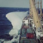 """""""Alemannia"""" 1972 ein modernes Frachtschiff   der IA-Klasse von Hapag. Hier auf derr Reise nach Fernost durchquert  sie die Biscaya und nimmt ein klein wenig Spritzwasser.  Man achte auch auf das Stückgut, mit dem das Hauptdeck vollgestaut ist. (C)  by H.Kobor"""